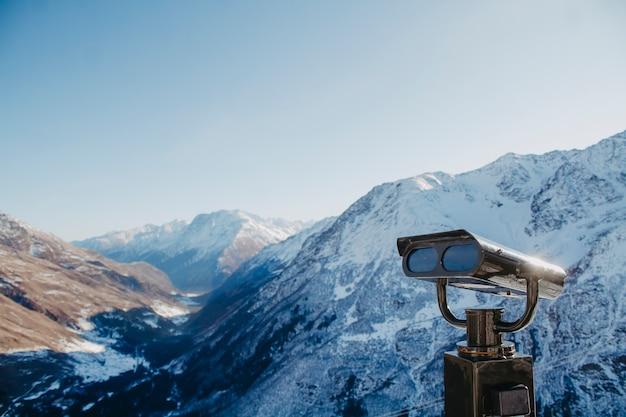 Binoculares en la plataforma de observación en el primer plano de las montañas.