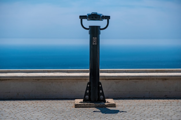 Binoculares que funcionan con monedas y fondo azul del mar. binoculares panorámicos públicos para observar la vista al mar.