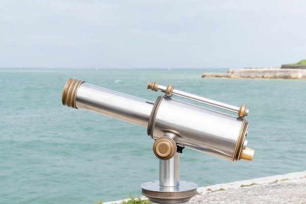 Binoculares telescopio oceánico turístico mira sobre la playa de agua