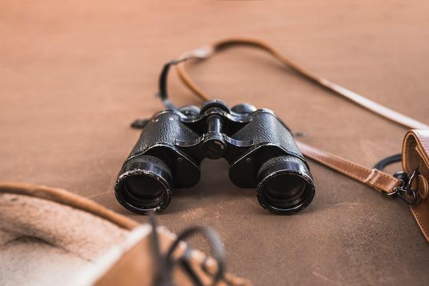Binoculares entre zapatos y bolso