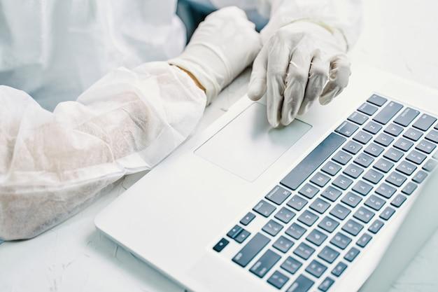 Bio peligro hombre con laptop. hombre usando una computadora portátil sobre una mesa en cuarentena.