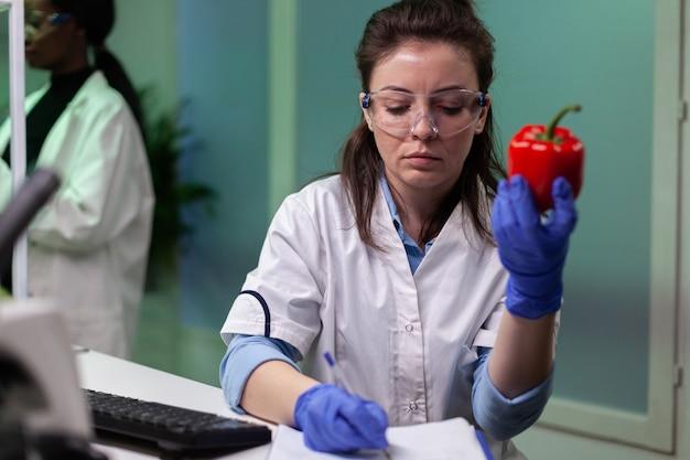 Biólogo mujer sosteniendo pimienta gmo escribiendo experiencia médica en microbiología