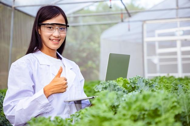 Biotecnólogo asiático hermoso que usa la computadora portátil para la investigación con el vegetal de la especie de la col rizada en la granja orgánica.