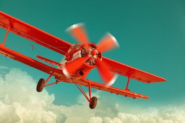 Biplano rojo volando en el cielo nublado