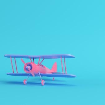 Biplano rosa sobre fondo azul brillante en colores pastel. concepto de minimalismo