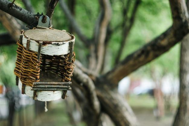 Birdhouse trenzado inusual en el árbol en el entorno urbano.