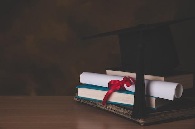Un birrete y un rollo de graduación, atados con una cinta roja.