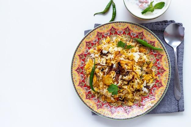 Biryani de pollo indio halal servido con yogurt tomate raita