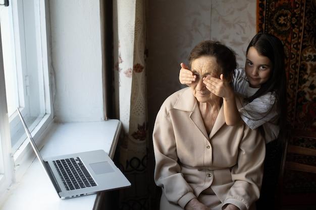 Bisabuela y nieta muy ancianas con computadora portátil en línea