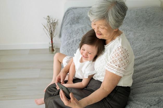 La bisabuela se sienta con su bisnieta y mira el teléfono inteligente.