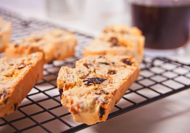 Biscotti italiano en la rejilla para hornear y un vaso de café en la superficie
