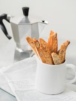 Biscotti - postre de almendra italiano tradicional con taza de café y cafetera moka en el periódico.