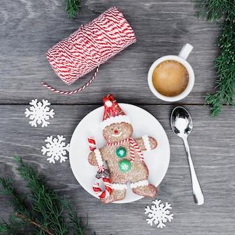 Biscuit muñeco de nieve en un plato cerca de una taza de bebida, copos de nieve e hilos