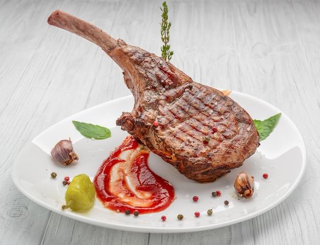 Bistec al hueso. tomahawk steak en una mesa de madera blanca. vista superior.