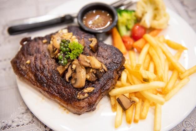 Bistec de carne asada con vegetales, hierbas, especias, pimienta negra, bistec de ternera a la parrilla con papas fritas