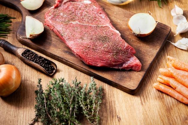 Bistec crudo sazonado con sal y papper listo para ser asado. proteína saludable. cebollas. filete sabroso.