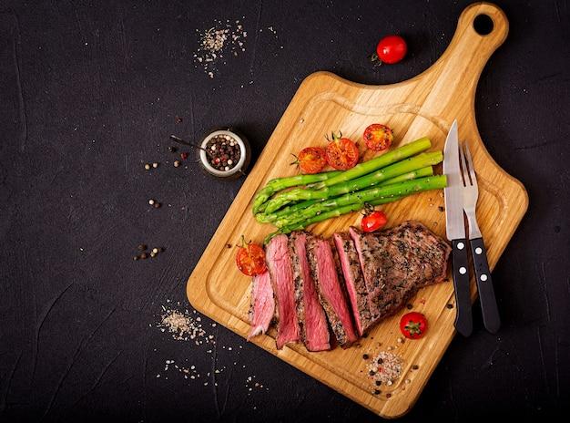 Bistec jugoso carne de res rara con especias en una tabla de madera y guarnición de espárragos.