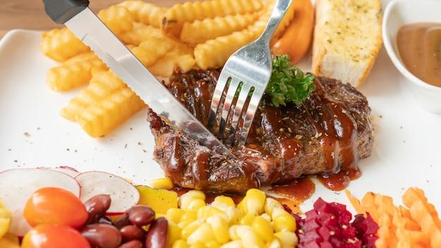 Bistec, papas fritas y vegetales en un plato blanco.