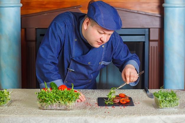 Bistec a la parrilla con micro-verdes y tomates en un plato cuadrado negro.