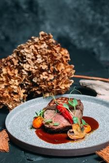 Bistec a la parrilla en un plato con pimiento picante sobre un fondo elegante