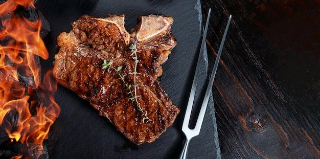 Bistec a la parrilla sobre una pizarra negra con tenedor para carne y brasas