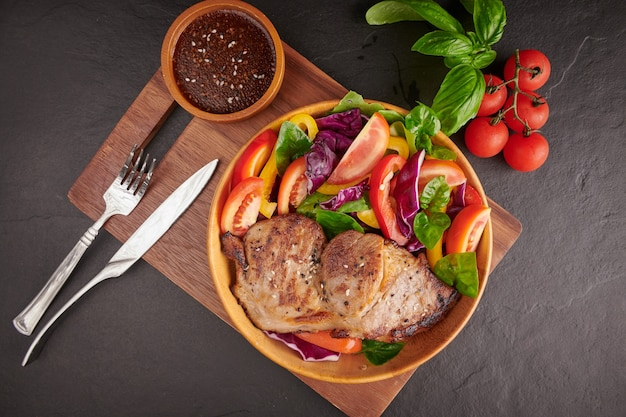 Bistec a la parrilla con verdura fresca, pimiento dulce, tomate, cebolla morada, pimiento rosa y especias. comida sabrosa casera. concepto de comida sabrosa y saludable. superficie de piedra negra. filete de cerdo con ensalada