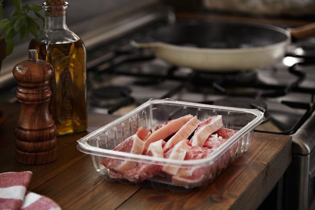 Bistec recién cortado junto a una estufa con sartén y aceite, pimienta y albahaca