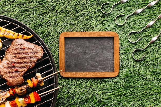 Bistec y salchichas a la parrilla en parrilla de barbacoa cerca de pizarra en blanco y pincho metálico sobre estera de hierba