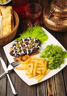 Bistec de ternera con papas fritas, ensalada verde, judías verdes y nuggets de pollo.