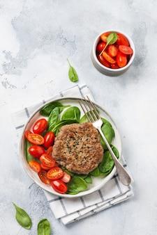 Bistec de ternera a la plancha con tomates cherry y espinacas, ajo, condimentos, pimientos y cebollas. plato tradicional serbio de pleskavitsa. vista superior