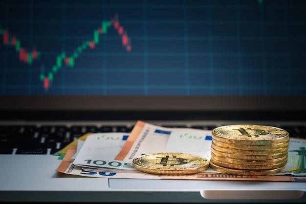 Bitcoin con billetes y monitores en euros, billetes de uero sobre teclado con gráfico de estadísticas de forex