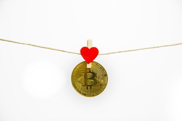 Bitcoin colgando con corazón rojo aislado sobre fondo blanco.