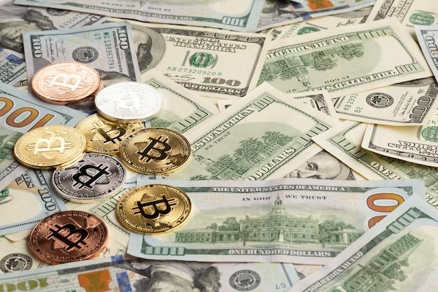 Bitcoin de diferentes colores sobre billetes de dólar
