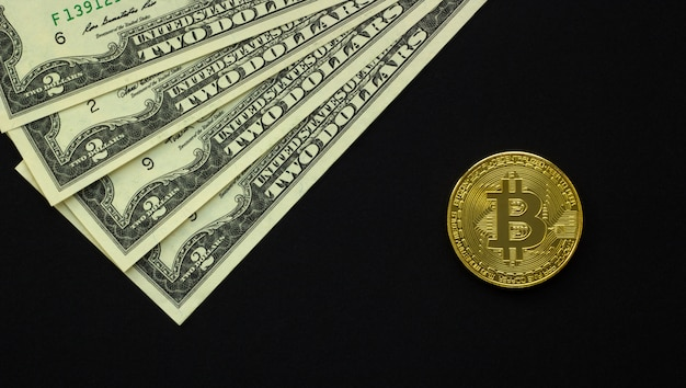Un bitcoin y dólares americanos sobre un fondo oscuro.