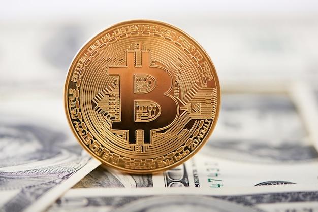 Bitcoin dorado cifrado en el borde como la mayor criptomoneda en el fondo borroso de los billetes de dólar.
