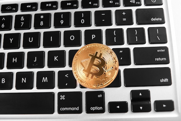 Un bitcoin dorado colocado en el teclado de la computadora portátil