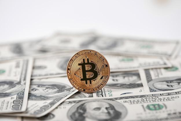 Bitcoin dorado como la criptomoneda más importante del mundo con billetes de cien dólares en el fondo