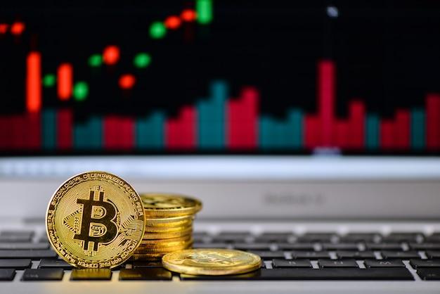 Bitcoin dorado en el teclado del portátil con gráfico en el fondo
