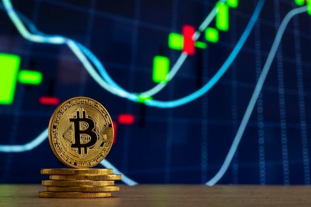 Bitcoin físico de pie en una mesa de madera frente a un gráfico azul