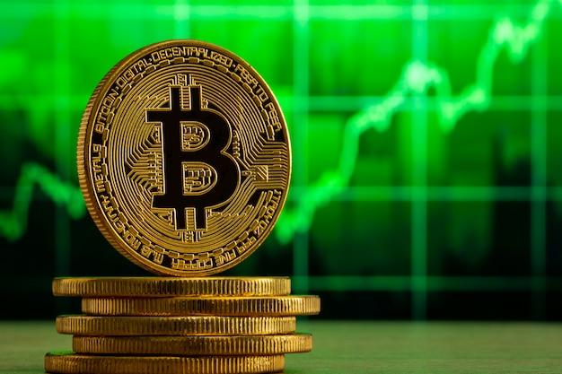Bitcoin físico de pie sobre una mesa de madera delante de un gráfico verde