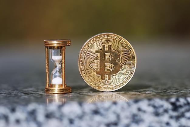 Bitcoin físico y reloj de arena que muestran que el tiempo pasa