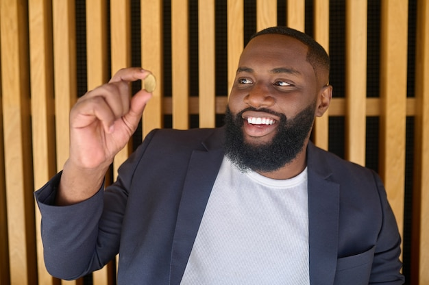 Bitcoin. un hombre de piel oscura con barba sosteniendo un bitcoin.