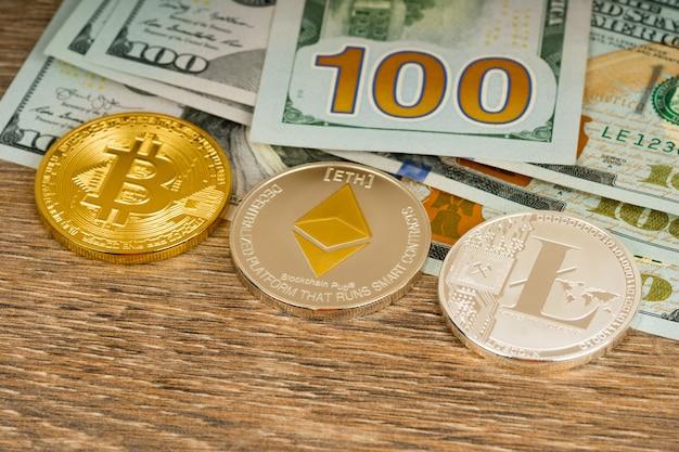 Bitcoin, litecoin y ethereum monedas metálicas sobre billetes de dólares