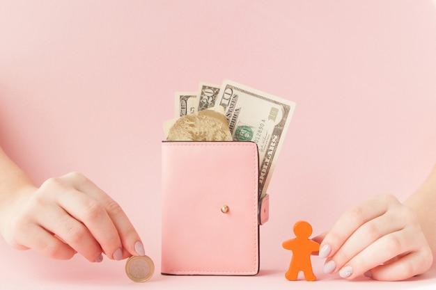 Bitcoin en una mano de mujer y dólares en billetera rosa con tarjeta de crédito en rosa.