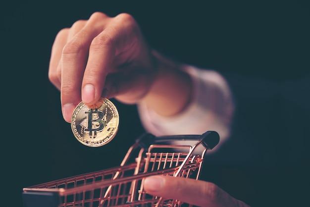 Bitcoin de oro en una mano de hombre, símbolo digitall de una nueva moneda virtual