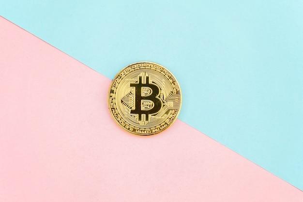 Bitcoin de oro en mesa geométrica pastel rosa y azul