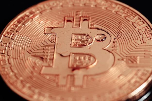 Bitcoin sobre fondo negro. la crisis económica mundial. bitcoin no es una moneda estable. fotografía macro
