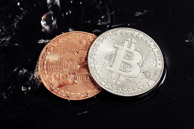 Bitcoin sobre fondo negro. lavado de bitcoin con agua. crisis económica.