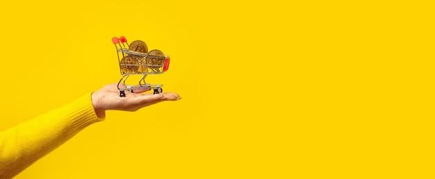 Bitcoins dorados en carrito de compras en mano sobre amarillo