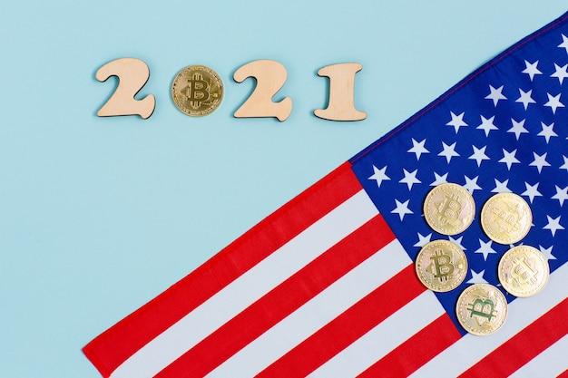 Bitcoins dorados con números de madera 2021 y bandera estadounidense sobre superficie azul